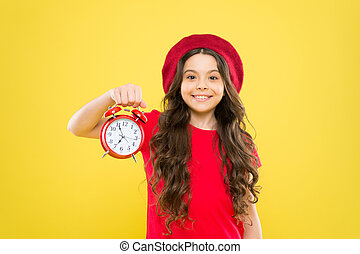 Shopping, sales and time concept. parisian child on yellow. child with alarm clock. Timeless fashion. happy girl with long curly hair in beret. beauty hairdresser. little girl in french style hat