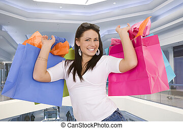 Shopping - Excited Caucasian woman holding shopping bags and...