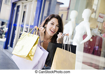 Shopping - Mid adult Italian woman holding shopping bags