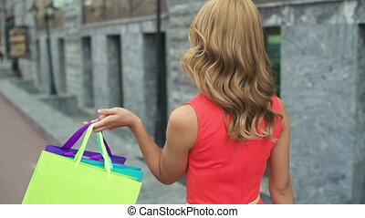 Camera following pretty girl strolling outdoors with shopping bags and turning to look straight at camera