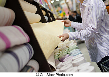 shopping time: man or woman holding or choosing rolls of...