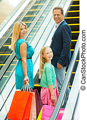 Shopping together is fun! Cheerful family holding shopping bags and looking over shoulder while moving up by escalator