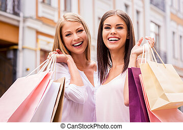 Shopping together is fun. Two attractive young women holding shopping bags and smiling while standing outdoors