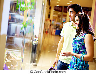 Shopping together - Tilt up of young couple standing in...