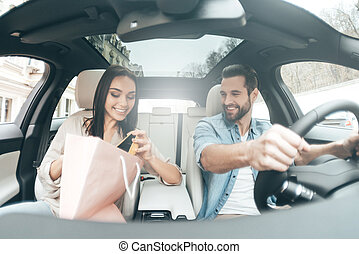 Shopping together. Young beautiful couple sitting on the front passenger seats and smiling while attractive man driving a car
