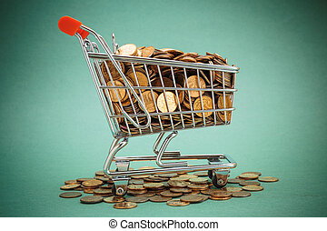 Shopping trolley with coins on a green background