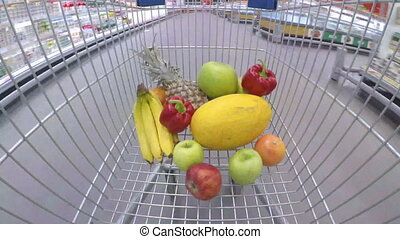 Shopping trolley with fresh vegetables and fruits moving through supermarket
