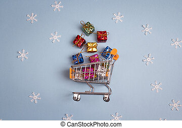 Shopping trolley with gift boxes on blue background.