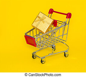 Shopping trolley with gold gift on a yellow background.
