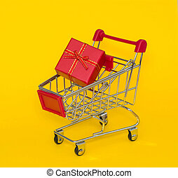 Shopping trolley with red gift on a yellow background.