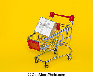 Shopping trolley with silver gift on a yellow background.