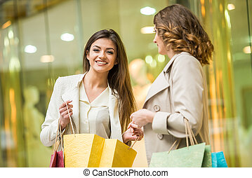 Two happy friends with shopping bag is shopping in mall.