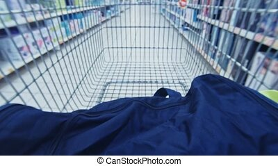 Inside view from basket driving on supermarket. Driving with cart in market aisle between shelfs. Shopping while wholesale, customer buying products. Shopper consumer making choice.
