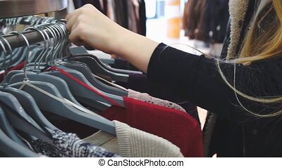 Shopping woman. Hands of shopper looking at clothes in clothes store. Close-up shot, handheld, slow motion 60fps, HD.