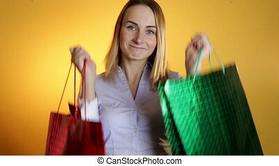 Shopping woman happy smiling holding shopping bags isolated on a yellow background. Lovely fresh young mixed race Asian Caucasian female model