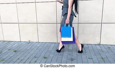 Shopping. Woman holding colored bags near her shooping mall in black friday holiday.