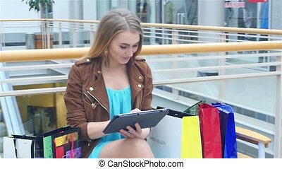 Shopping Woman holding Digital Tablet on bench the trading floor. Slow motion