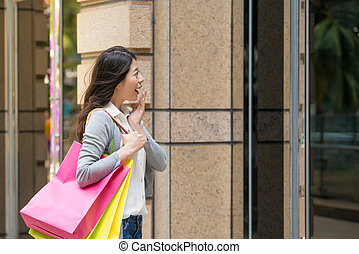 Shopping woman looking at clothing window display