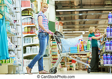 Shopping woman with cart at supermarket