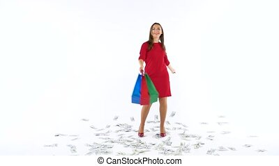 Shopping woman with multicolored shopping bags dances among scattered dollar bills on white background in studio. Let's go holiday shopping concept. Slow motion