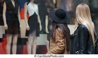 Shopping women looking at clothing store window - Shopping...