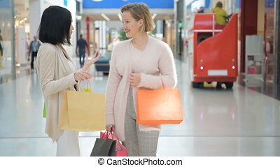 Shopping women talking happy holding shopping bags having fun laughing. Two beautiful young woman girlfriends in a shopping mall.