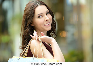 Young beautiful woman with shopping bags in stores