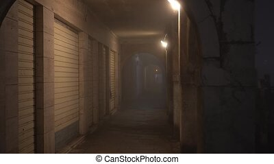 Shops closed with old shutters in illuminated arch passage on dark embankment near channel in ancient Chioggia city at foggy night