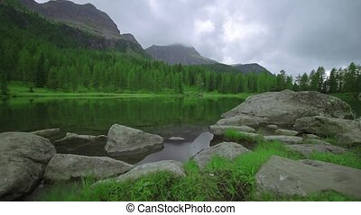 Shore of a lake covered by grass and rocks in front of the tall mountains