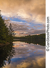 Shoreline of a lake under a colorful evening sky