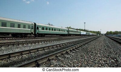 Short train passes by on railway,  traffic on bridge far
