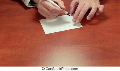 Short written advice Fake - Adviser%u2019s hands writing the...
