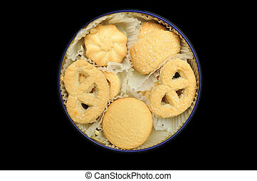 Shortbread cookies in a round tin isolated on black ...