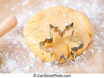 Shortcrust pastry dough with cookie cutter on a floured surface