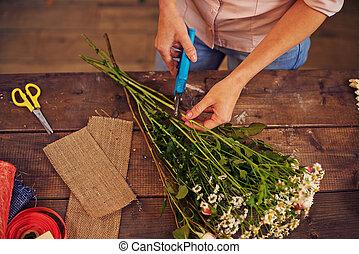 Shortening floral stems - Female florist cutting floral...