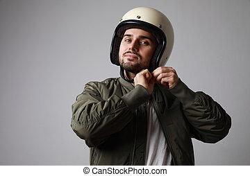 Shot brutal bearded biker man adjusting his white helmet in a green bomber jacket. Free space for text.