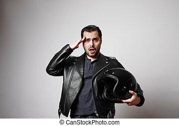 Shot brutal bearded biker man holding helmet dressed in a black leather jacket. Free space for text.