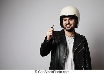 Shot brutal bearded biker man holding motorcycle keys and dressed in a black leather jacket. Free space for text.