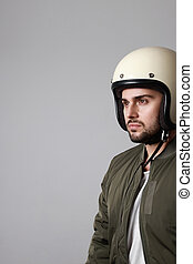 Shot brutal bearded biker man wears helmet and dressed in a green bomber jacket. Free space for text.