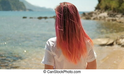 Shot from back of girl with red orange hair standing on shore of river