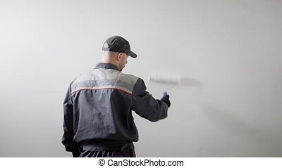 Shot from behind of a hired builder painting side wall in...