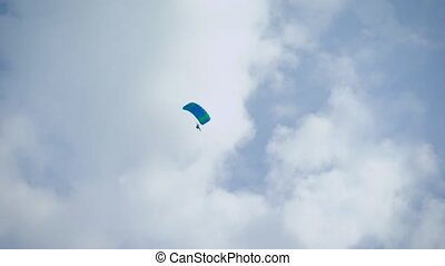 Shot from the land of a skydiver glinding in the skies,...
