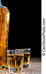 Shot glass with Whiskey (close-up shot) on wooden background