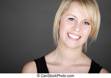 Beautiful Smiling Blonde Girl against Grey Background