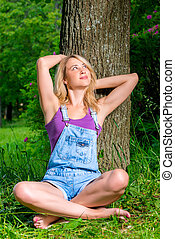 shot of a beautiful young girl in a park near a tree
