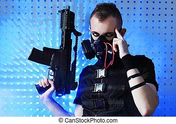 Shot of a conceptual man in a respirator holding a gun.