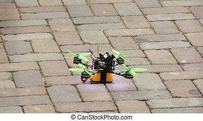 Shot of a drone that taking off, A small drone takes off from paving stones