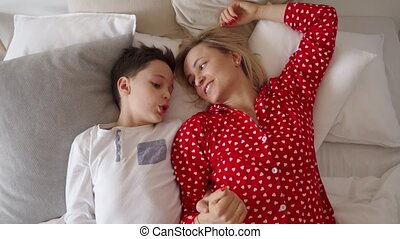 Shot of a little boy laying on a bed with his mother and speaking