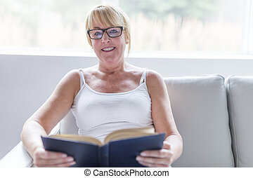 Shot of a mature woman reading her favorite novel while at home in living room.