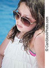 Shot of a Pretty Child in Sunglasses Sitting Next to the Pool